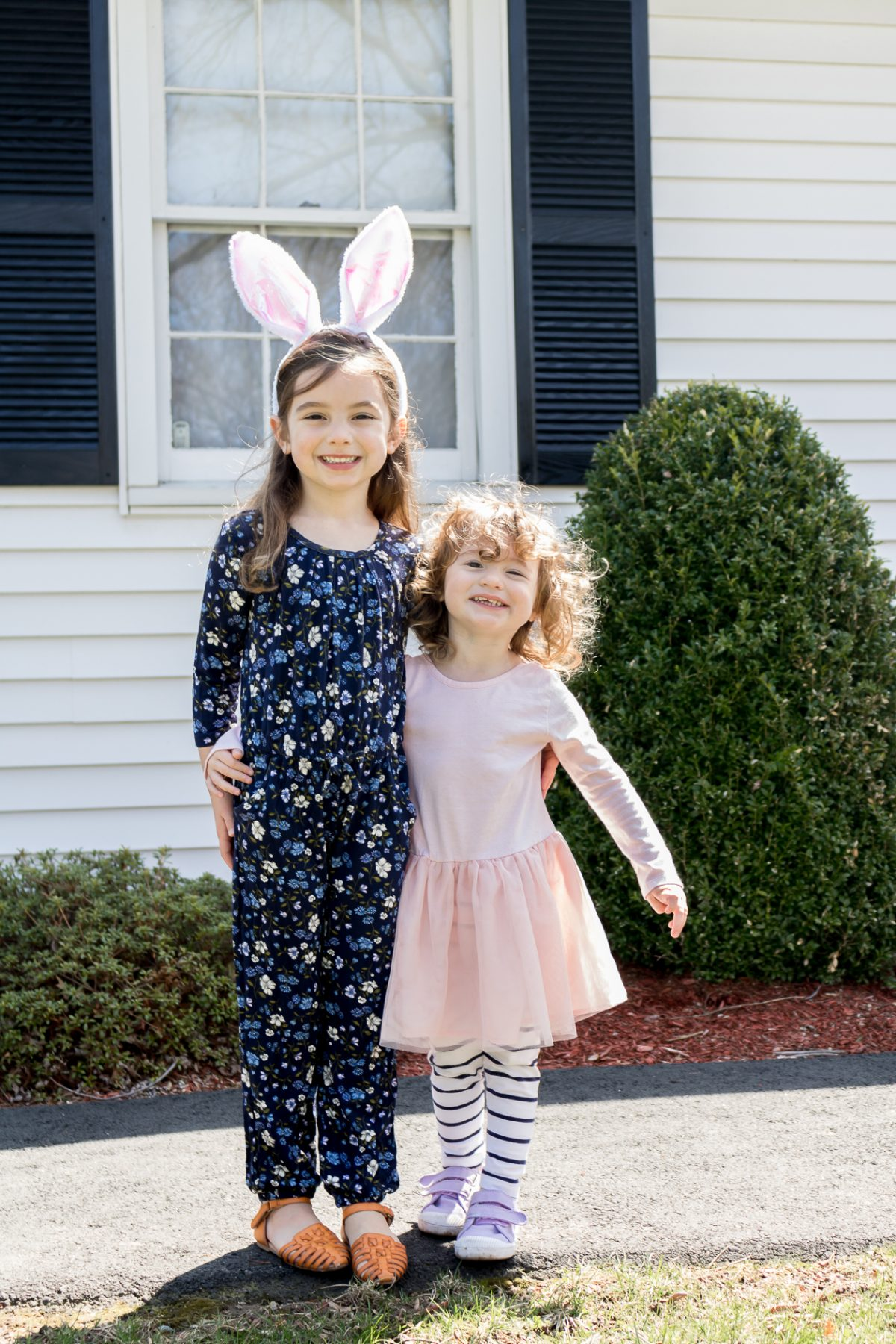 Little girl wearing blue jumpsuit and bunny ears and another little girl with curly hair wearing a pink dress and blue striped pants