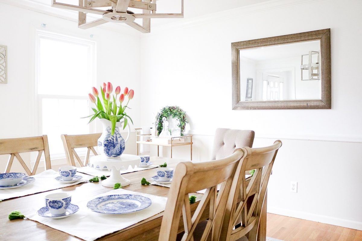 Dining room set with blue china and beautiful tulips in the center of the room