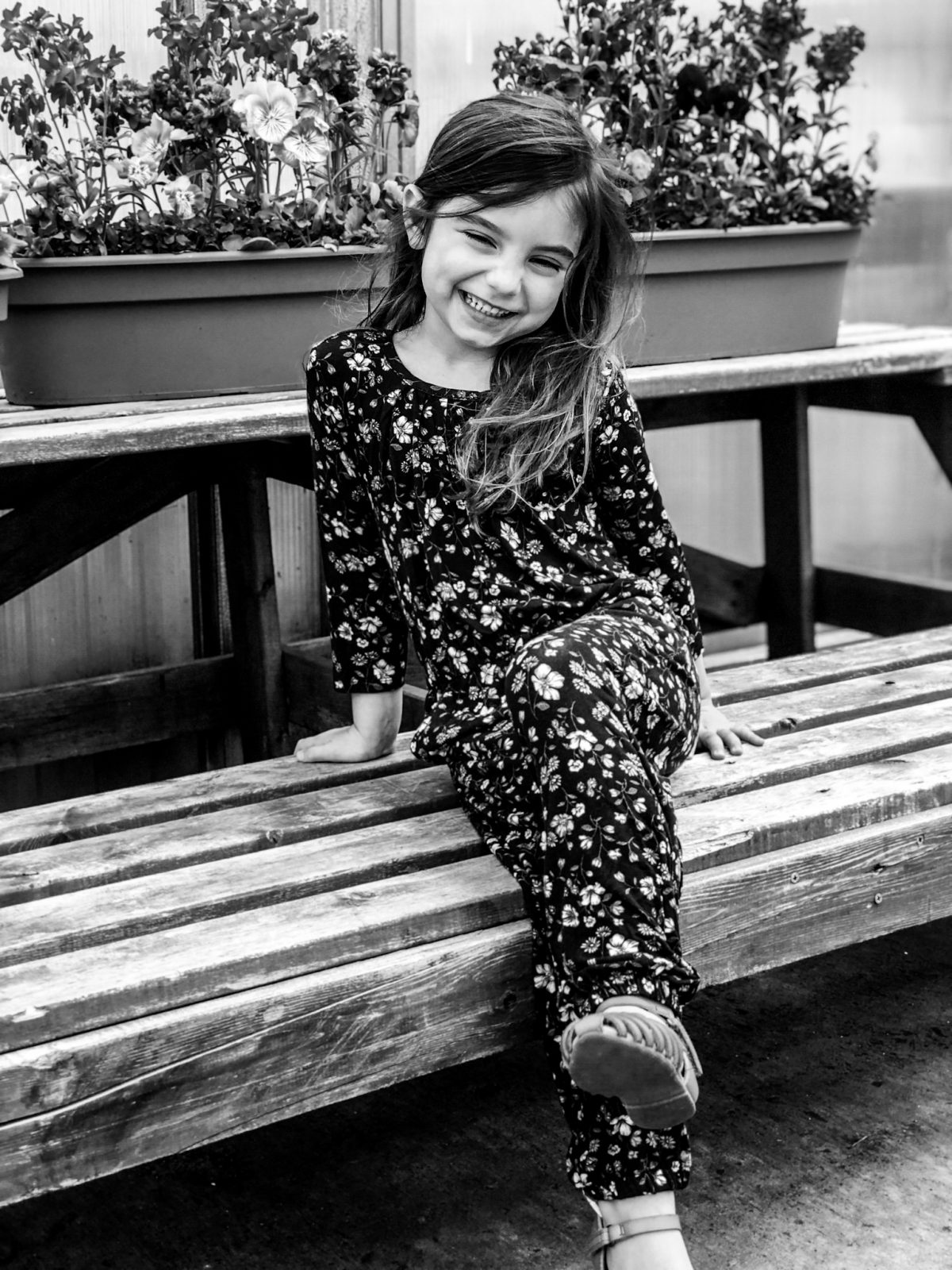 smiling little girl sitting on a bench in black and white