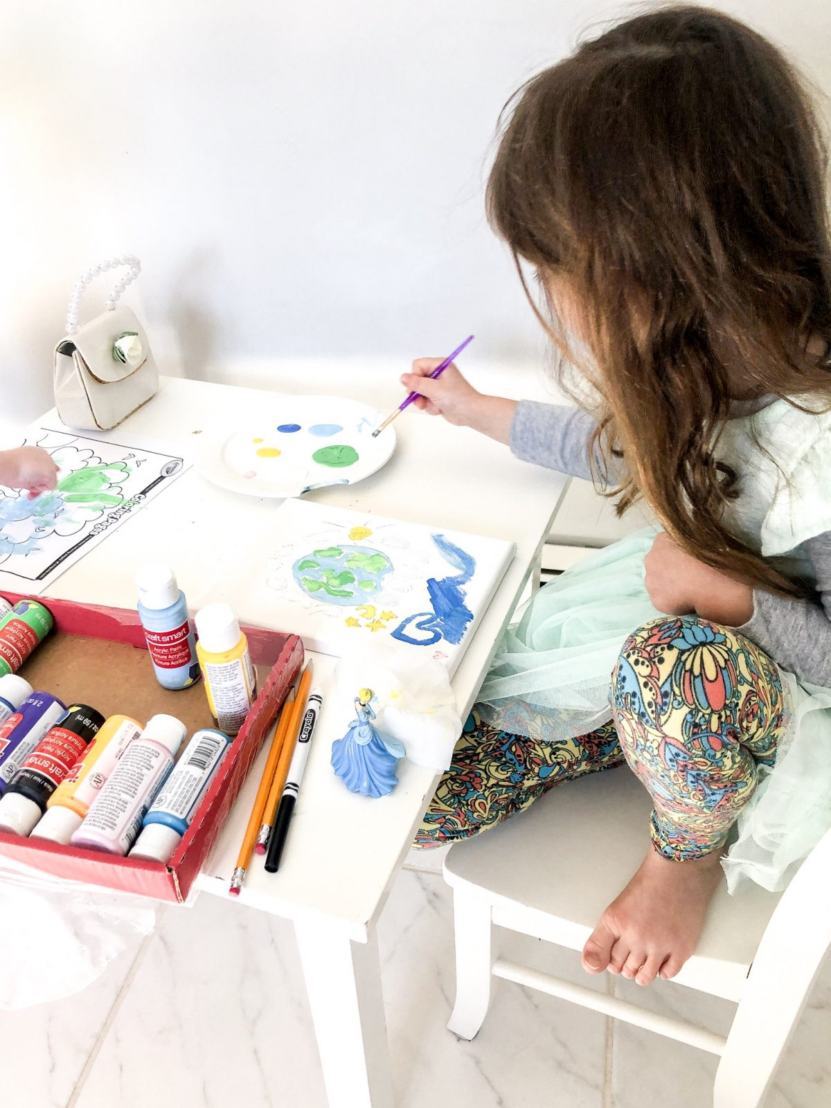 Little Girl painting a picture of the earth on a canvas