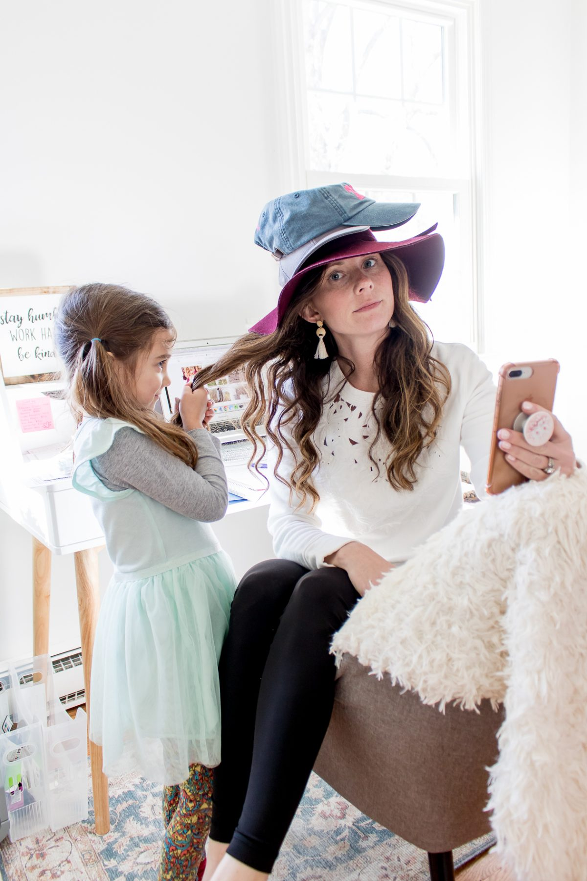 mom wearing three hats looking at the camera and holding a phone while her daughter pulls her hair