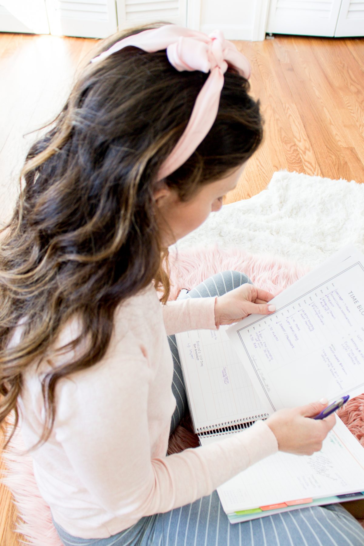 woman wearing a pink bow in her hair and pink sweater looking at a time blocking worksheet