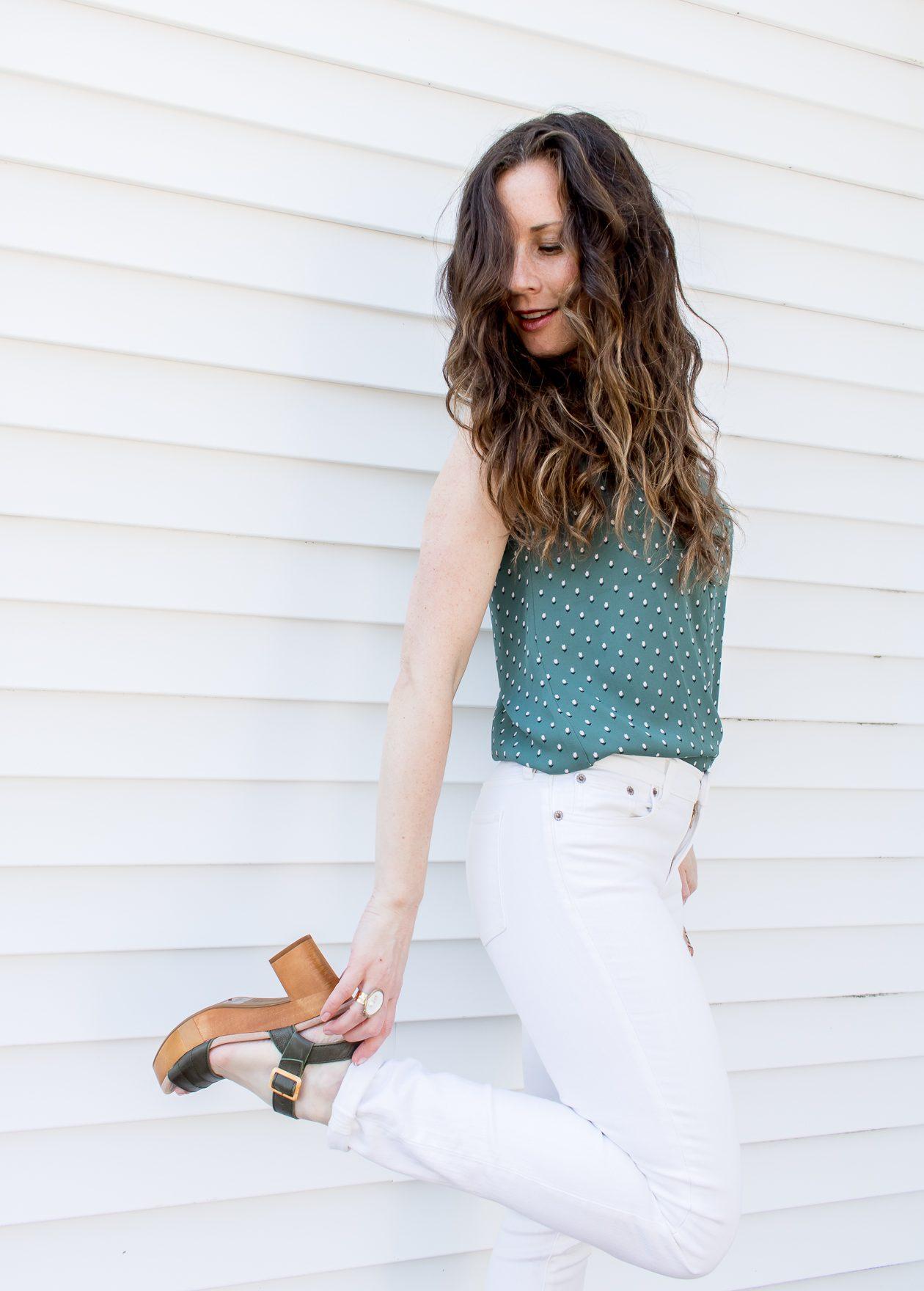 Woman holding platform sandal wearing white denim with green tank