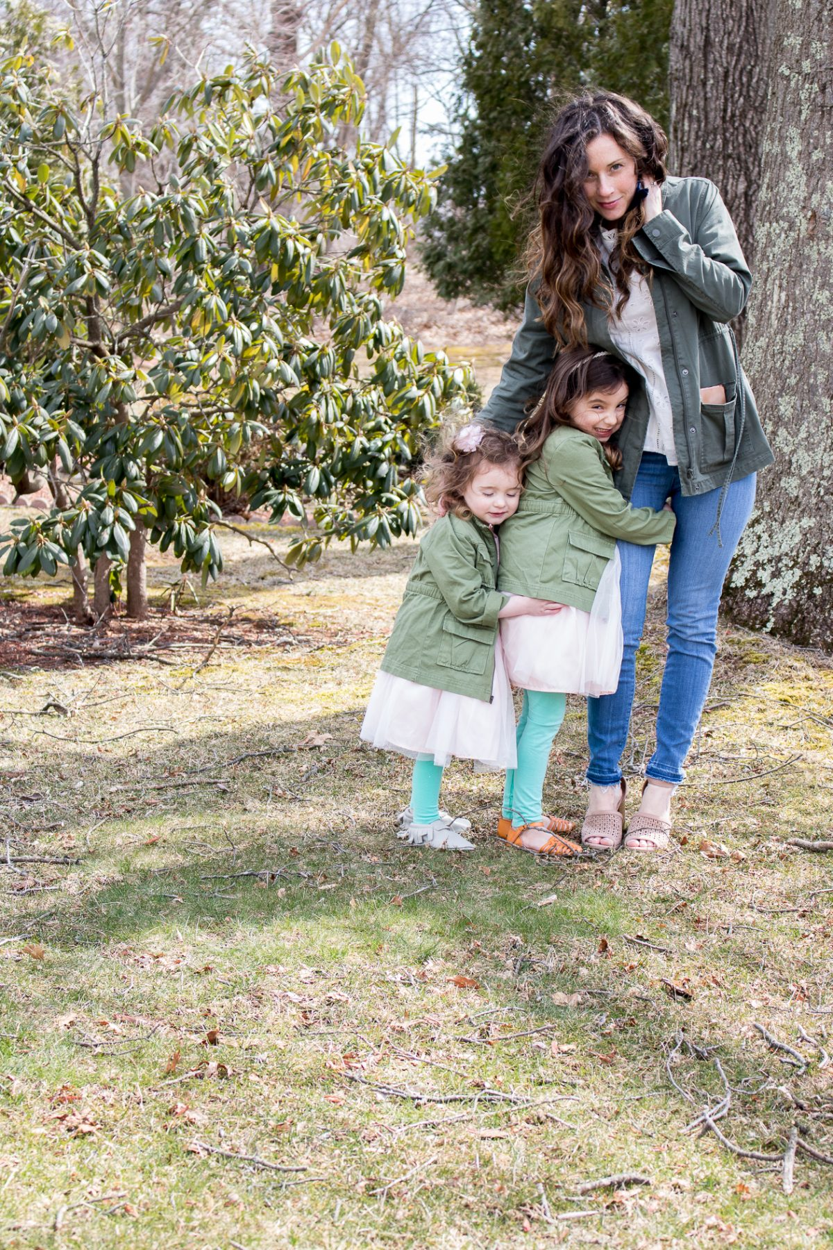 Woman wearing a green coat looking at the camera as her daughters hold on to her leg - Five Reasons Not to Exercise