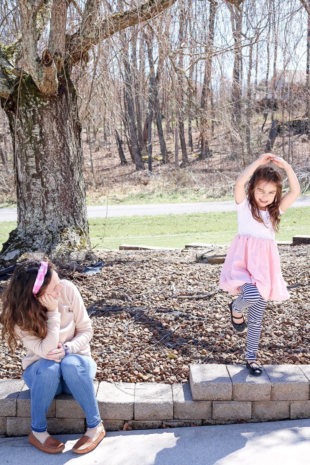 Mom wearing pink headband, tan dudley stephens fleece, moccasins, looking at little girl wearing pink dress and standing in a passe