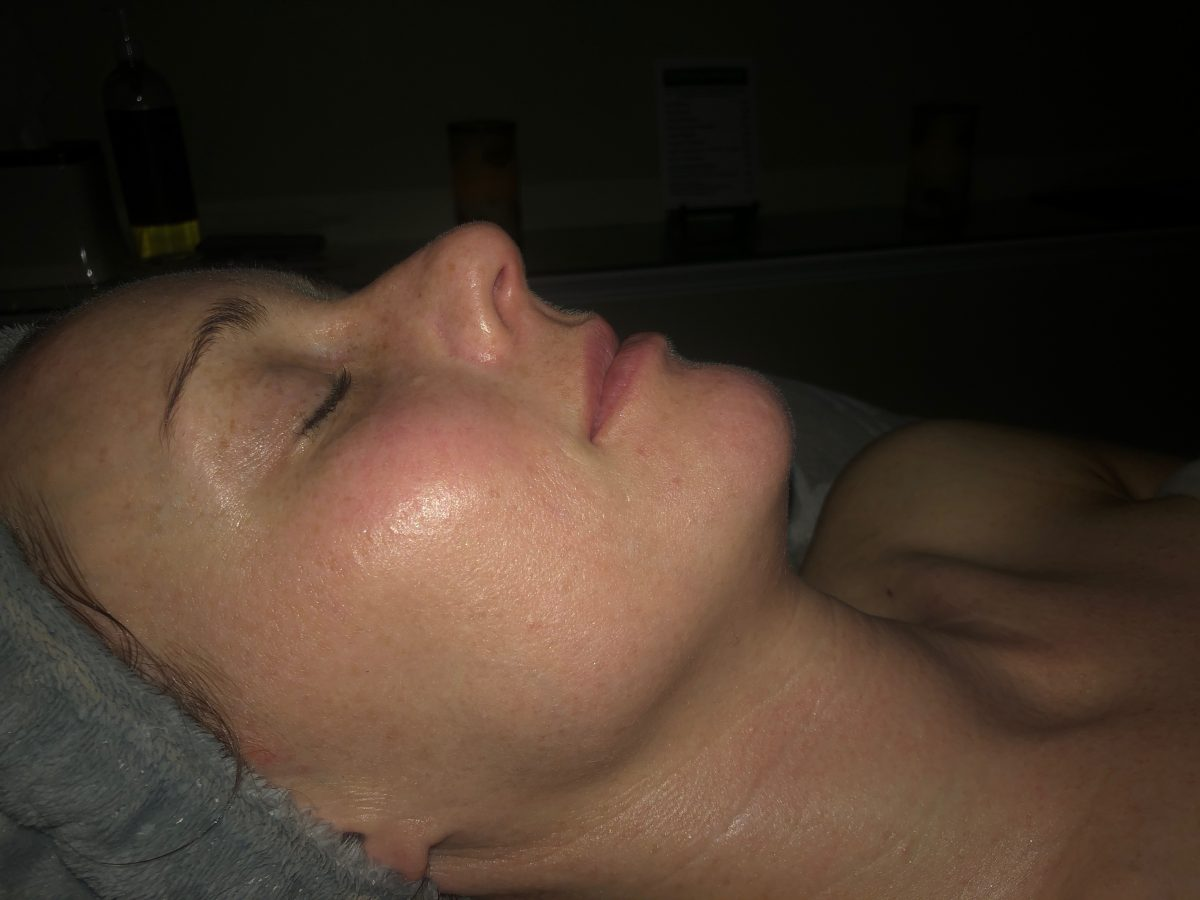 Woman's side profile, her eyes are closed and her skin is glowing from a facial at a spa