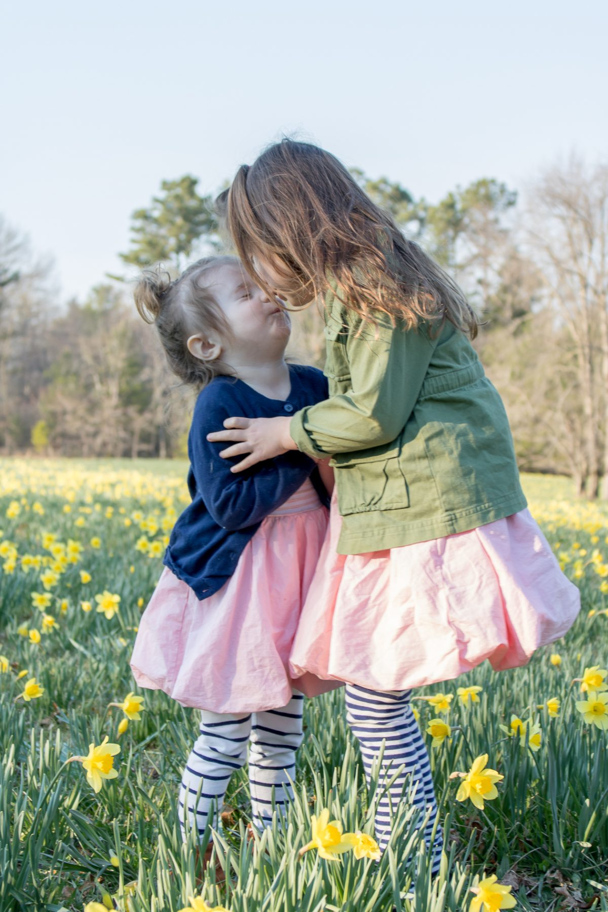 Sisters in a daffodil field, big sister wearing a green coat and pink dress kissing little sister on the nose
