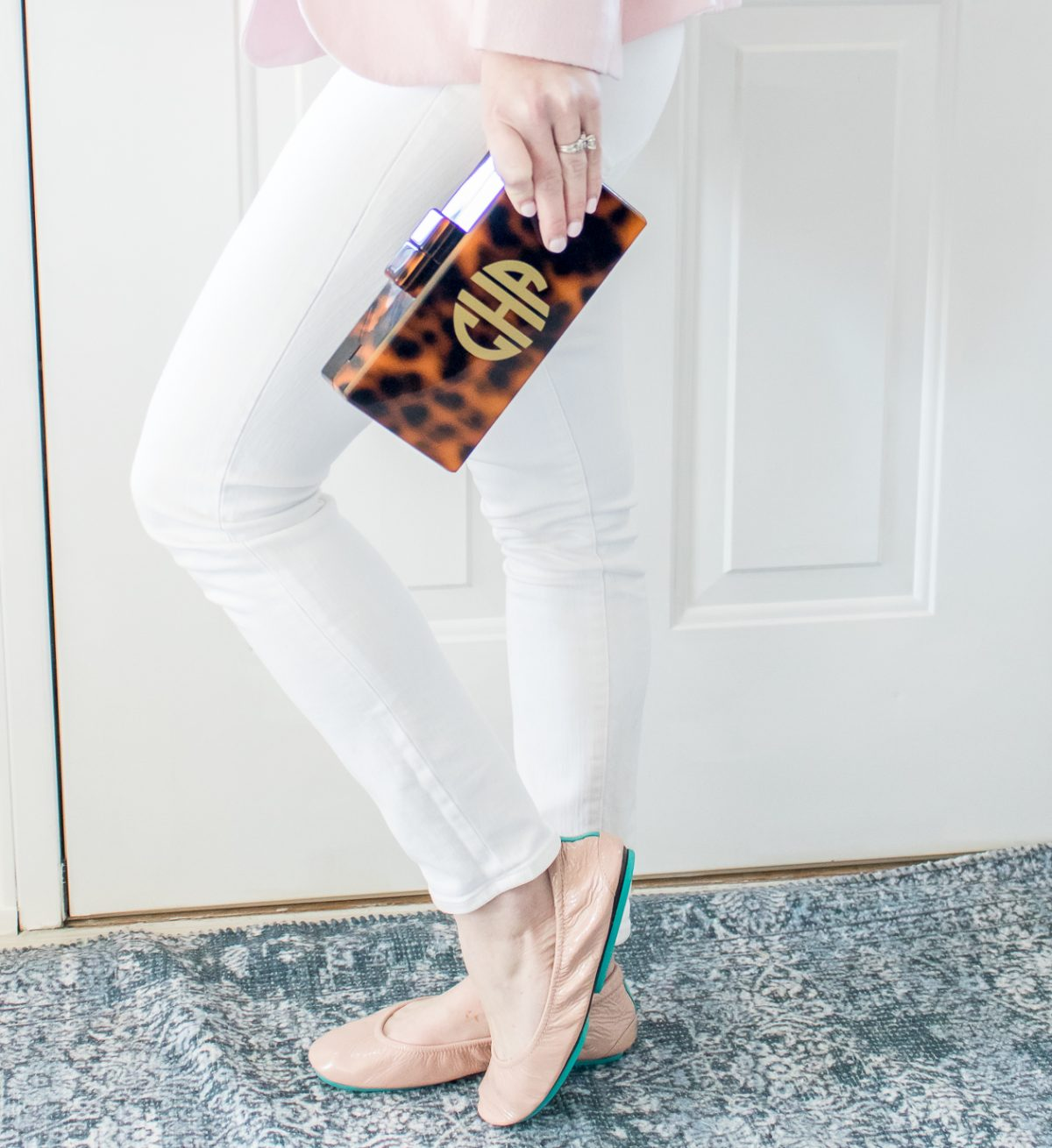 Woman in pink blazer and white pants holding tortoise shell clutch standing in front of a white door on a blue rug with foot popped wearing Tiek Ballet Flats showing