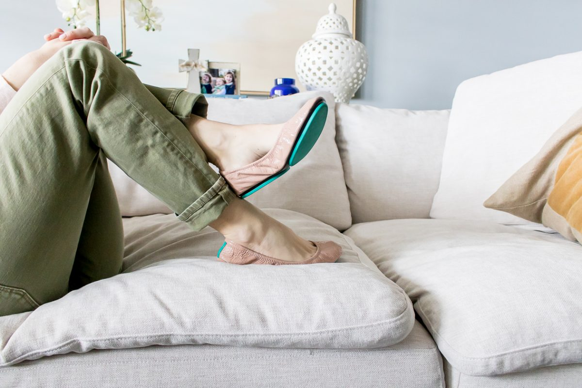 Woman's legs crossed wearing green pants and pink Tieks ballet flats with teal bottoms