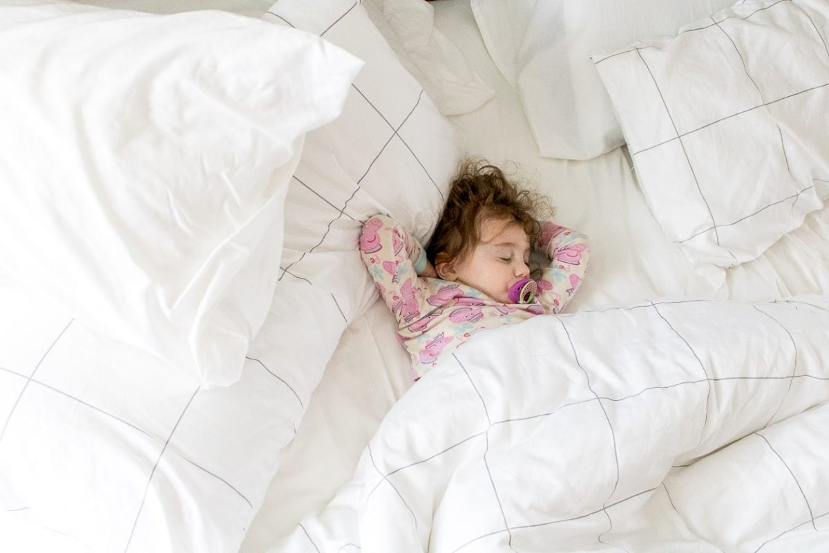 Little girl sleeping peacefully in bed with arms above her head