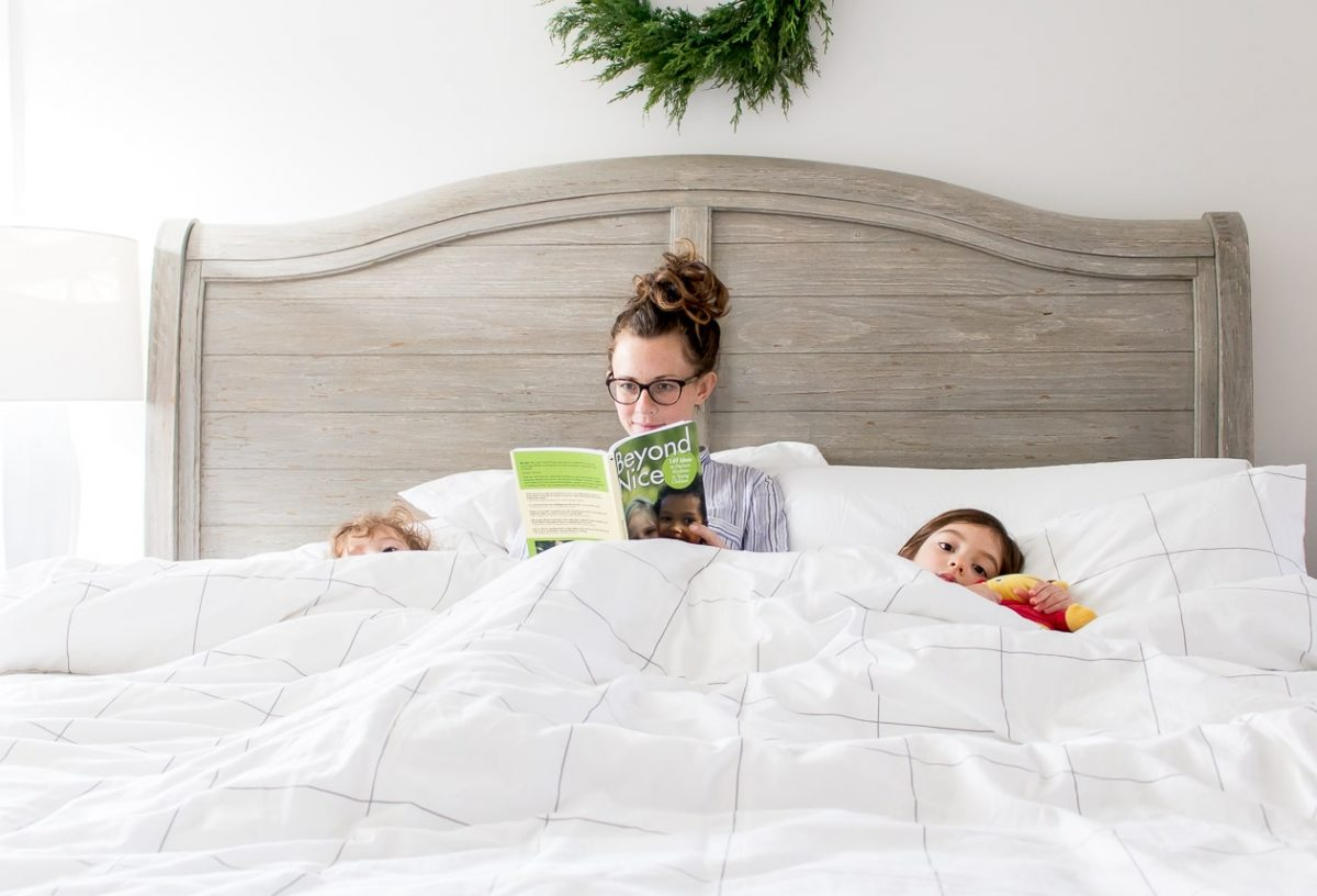 Mom in bed with little girls reading a book