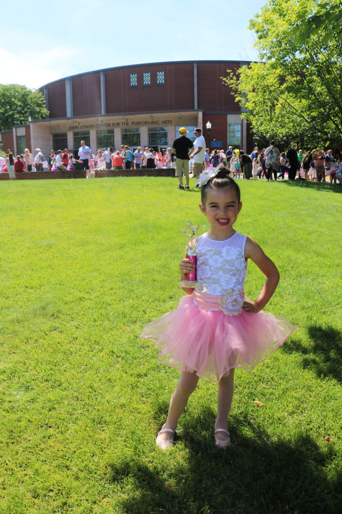 Ballerina after her dance recital holding trophy