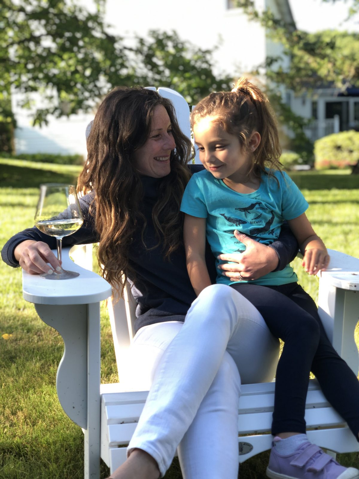 Mom and Daughter sitting in white Adirondack Chair