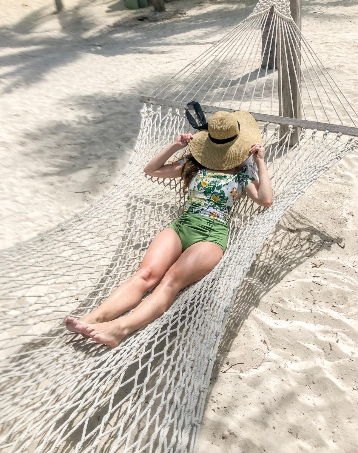 Woman Sleeping in Hammock with Hat Over Head in Kortni Jeane matching swimwear