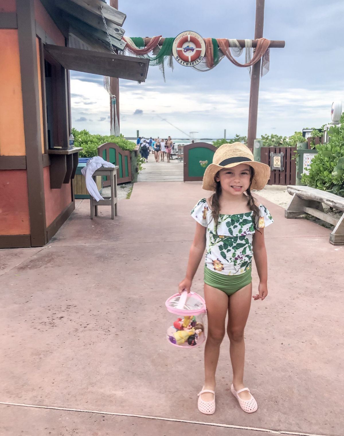 Little girl in green floral swimsuit by Kortni Jeane