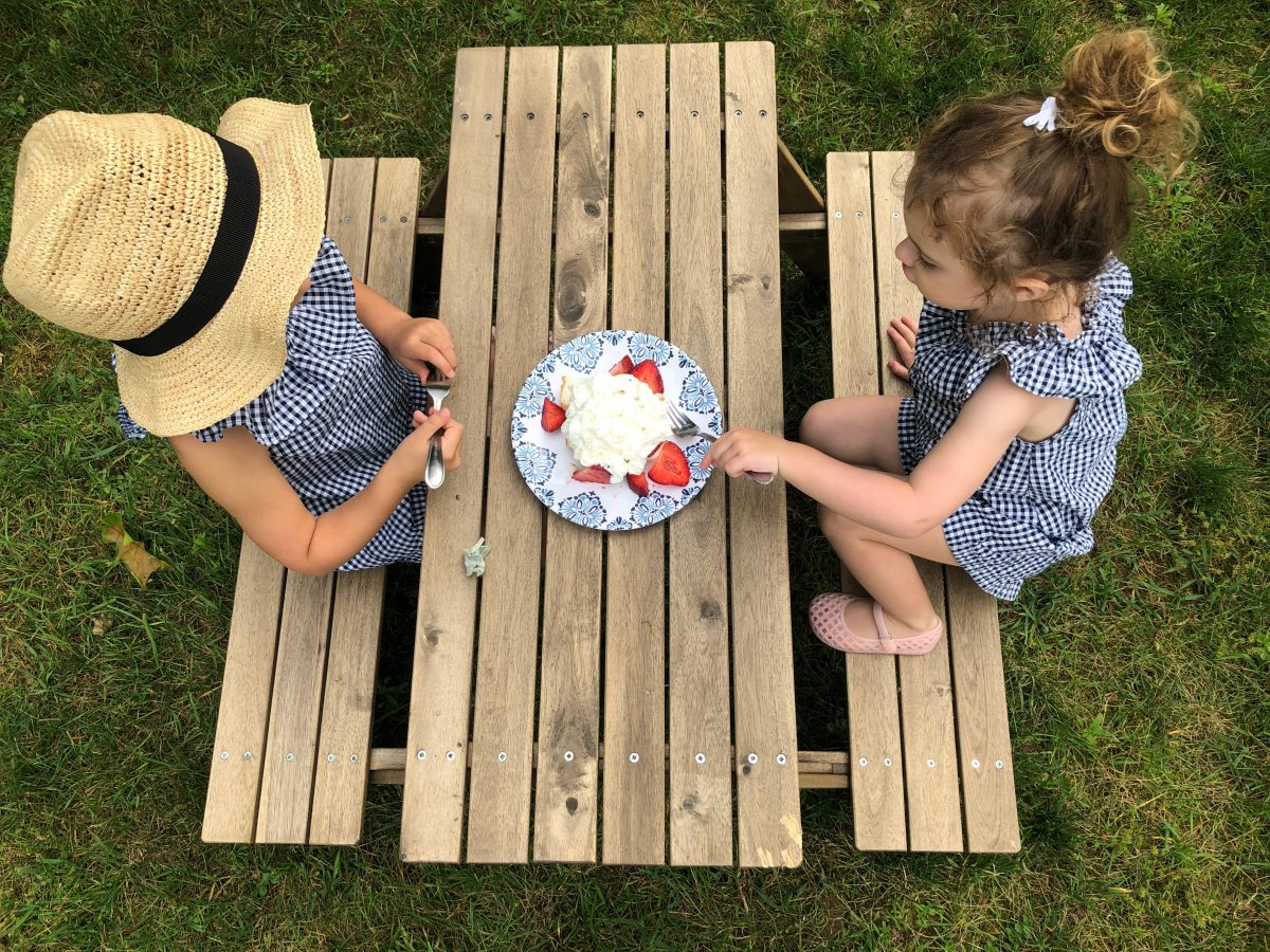 kids eating strawberry trifle at picnic table