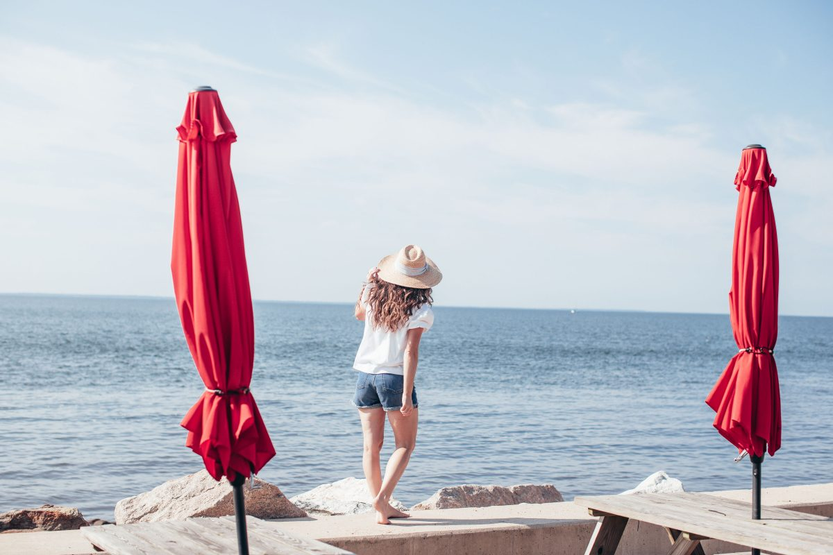Woman wearing beach hat standing between two red umbrellas on beach wall