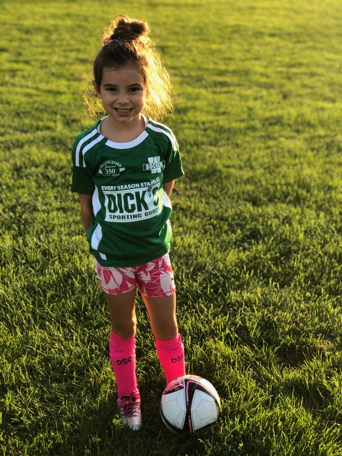 Little girl in green soccer shirt with soccer ball