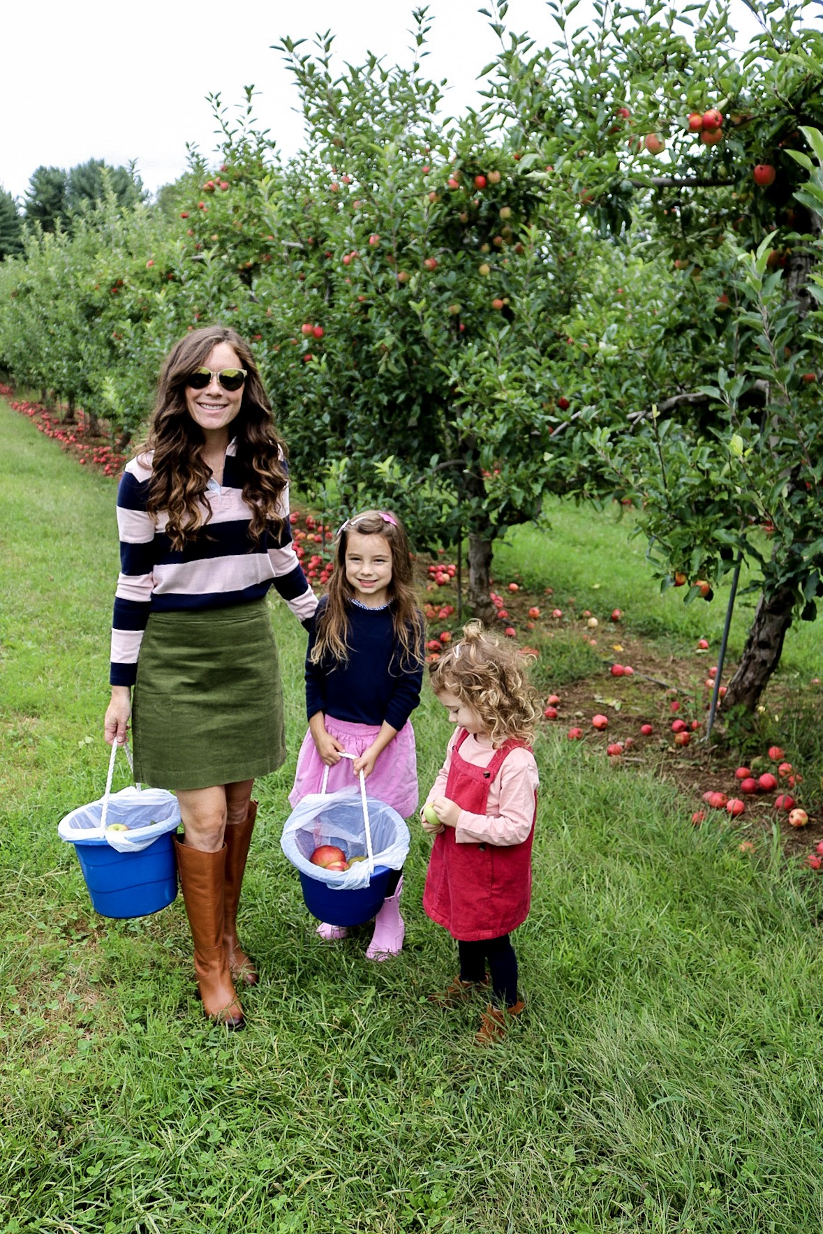 Woman in boots and corduroy skirt apple picking with little girls wearing dresses