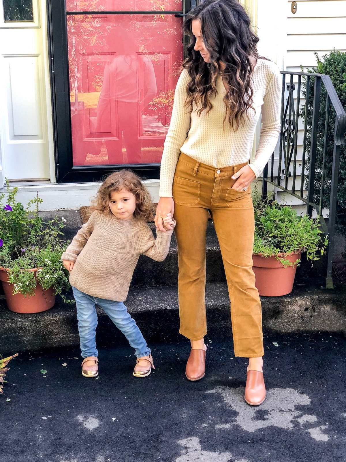 Woman wearing Cropped Corduroy Denim, Waffle Henley, Leather Mules with a little girl in a knit sweater and denim