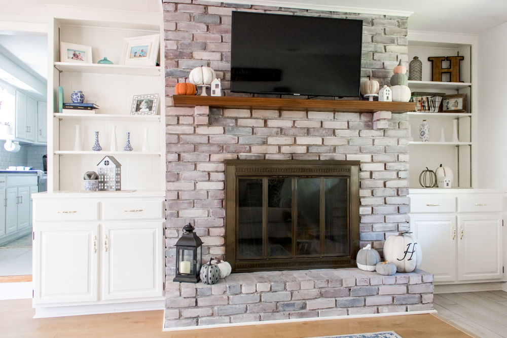 White Brick Fireplace Mantle and Built in Book Shelves Decorated for Fall with Neutral Colors
