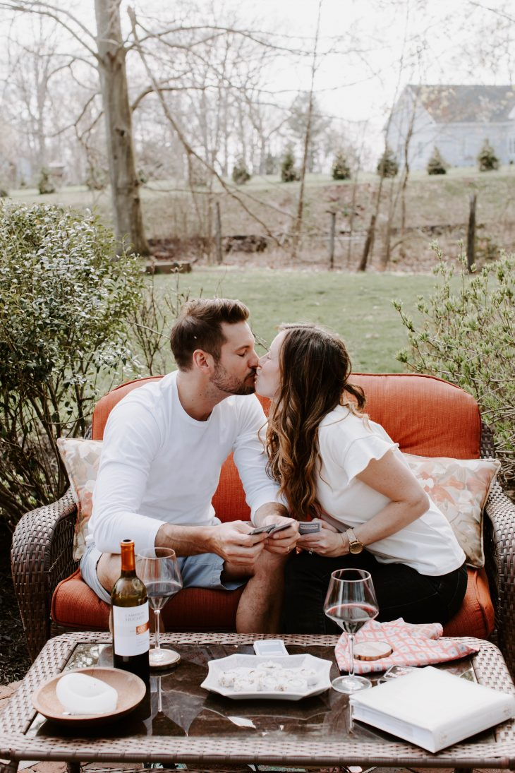 Man and Woman holding cards and kissing on outdoor couch