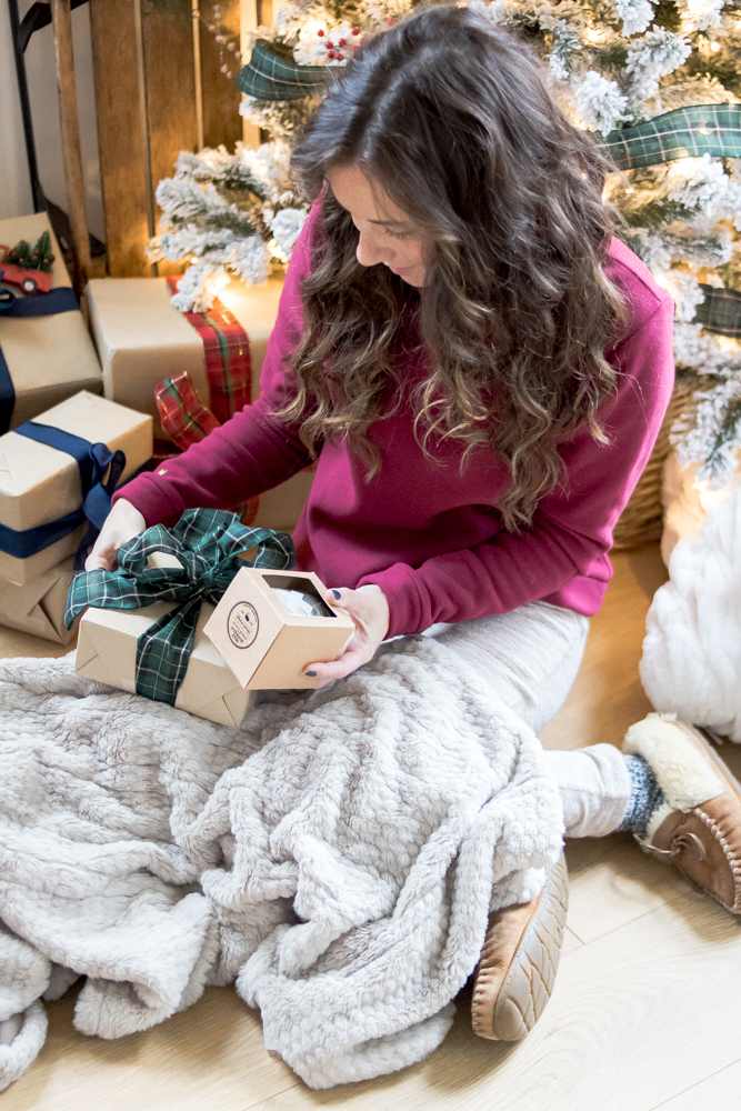Woman looking at candle and christmas present under a blanket in front of a christmas tree