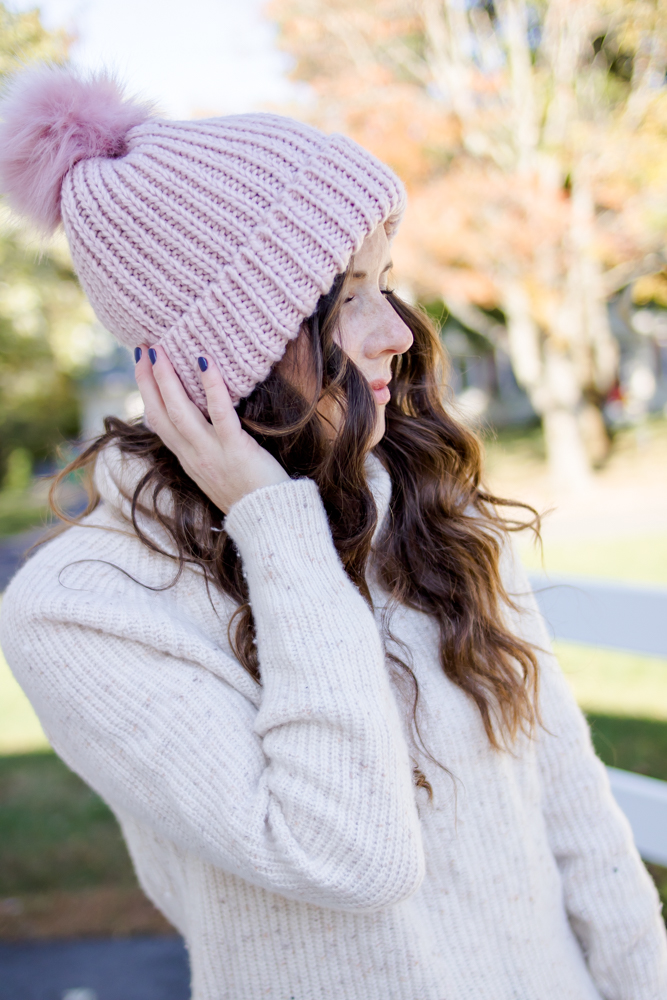 woman wearing pink winter hat with fur top and white sweater