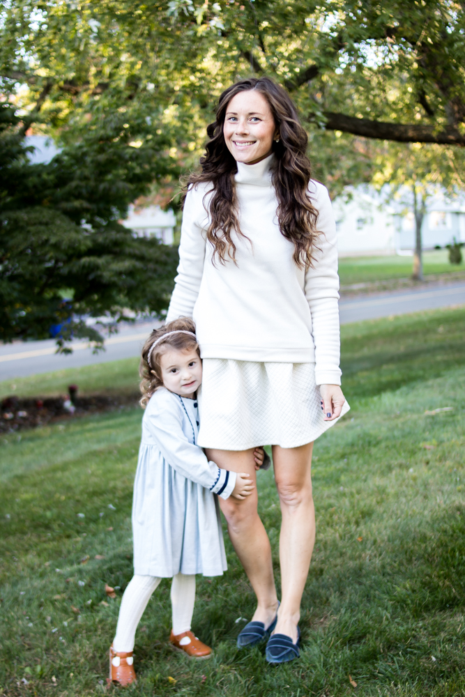 Mom and Daughter standing outside wearing white and blue outfits