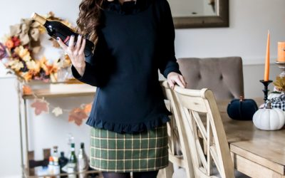 woman wearing black ruffle top and yellow tweed skirt holding wine bottles for thanksgiving outfit