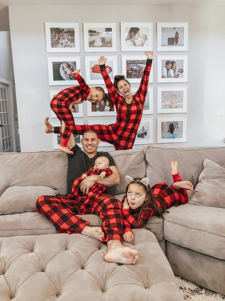 Family Being Silly Wearing Matching Christmas Pajamas