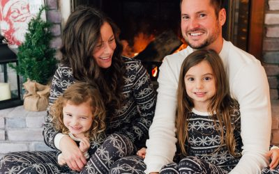 family in matching pajamas sitting by fireplace christmas