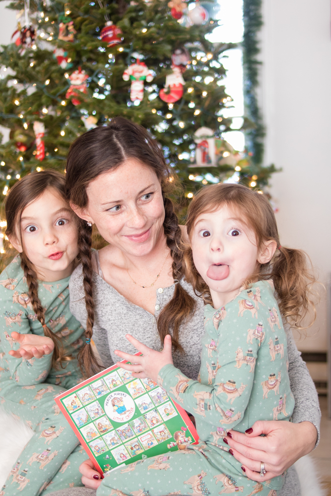Mom looking at daughters making silly faces wearing pajamas in front of Christmas tree after stomach flu subsides