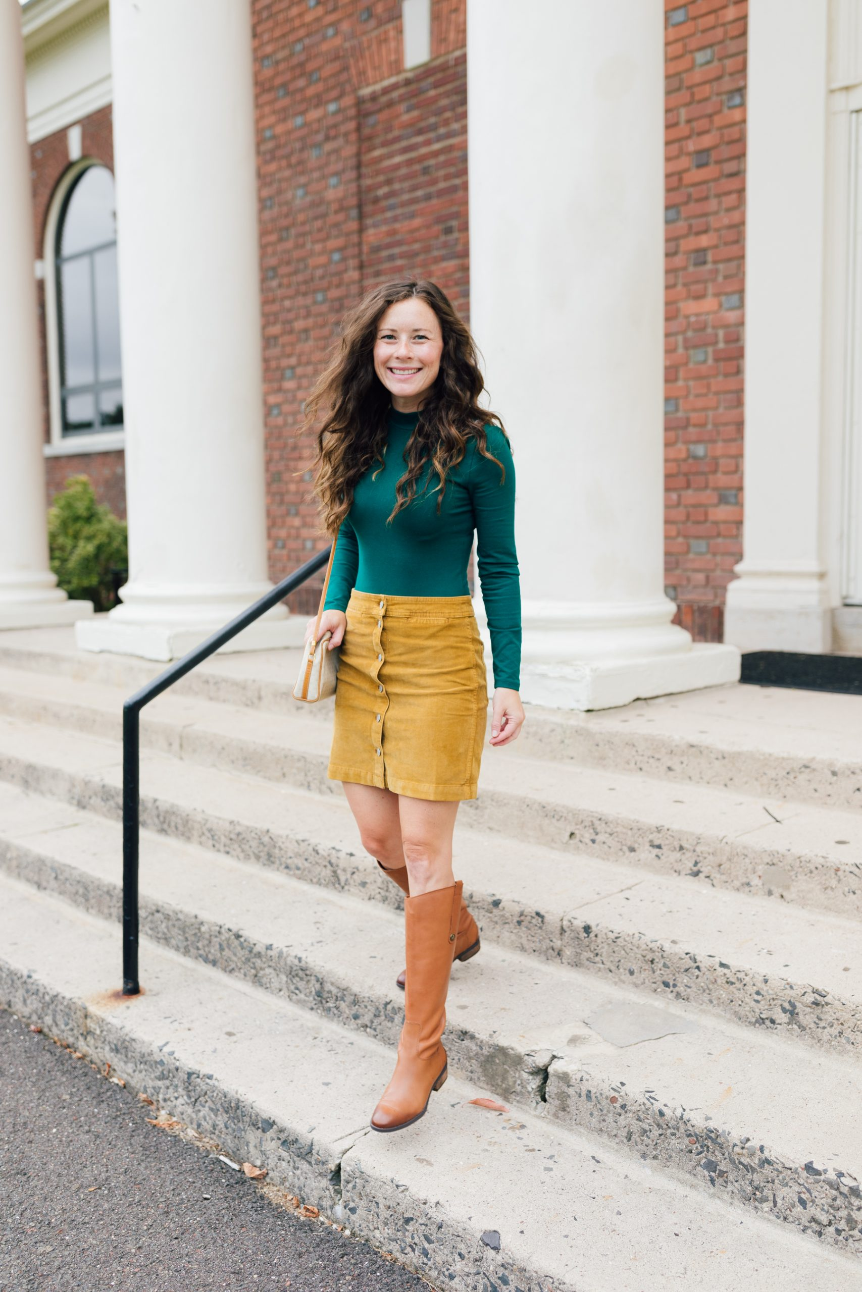 Woman in green top and yellow skirt with camel knee high riding boots smiling at Choate Rosemary Hall