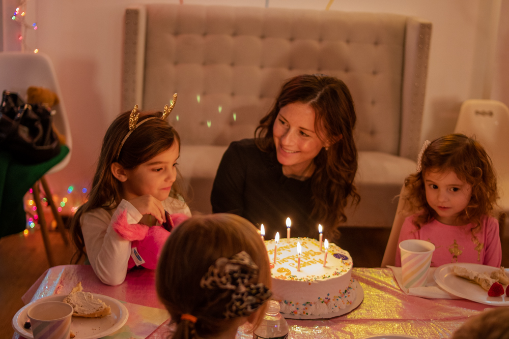 mom smiling at daughter sitting in front of birthday cake with lit candles