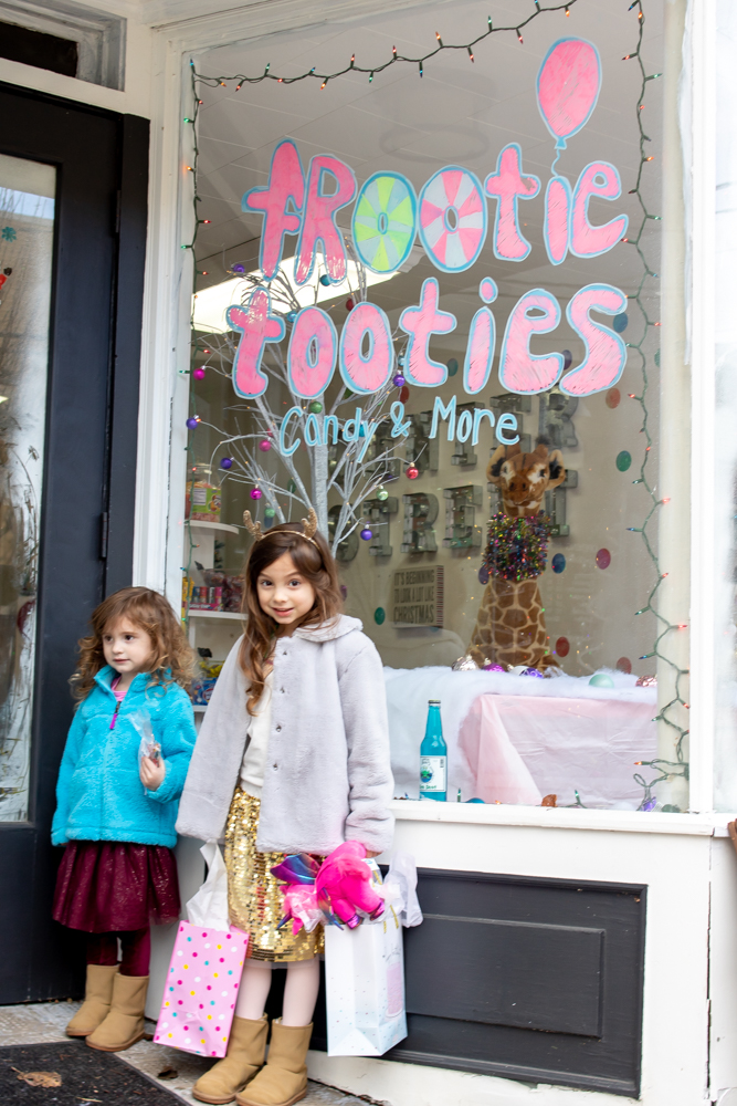 little girls standing outside frootie tooties candy store