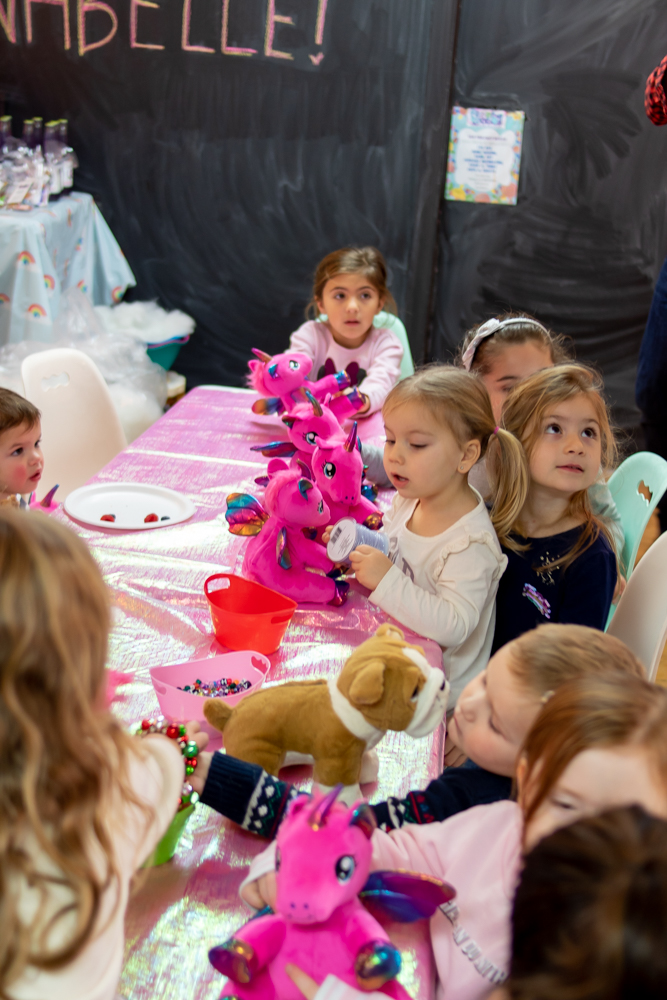 little girls sitting at craft table with stuffed unicorns