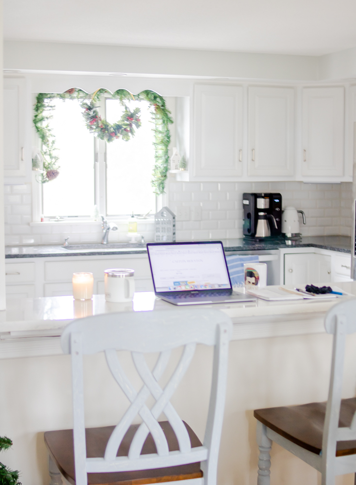 Pass through from dining room to kitchen with white quartz counter and Ew David Schitt's Creek mug on counter with laptop