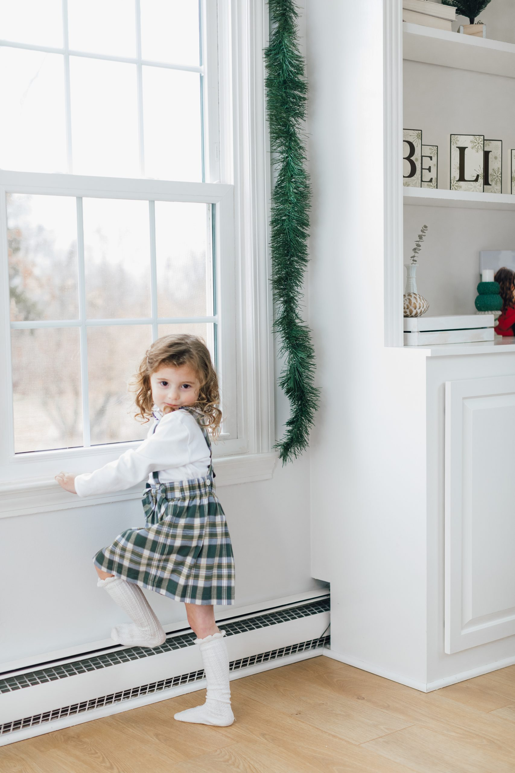 little girl making a sassy face while standing at a window