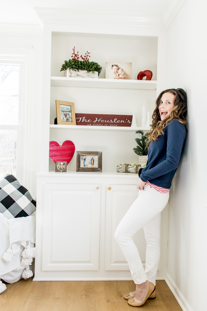 Woman wearing Blue Dudley Stephens Fleece with Red Stripe Shirt and White Denim in front of White Shelves with Valentine's Day Decor