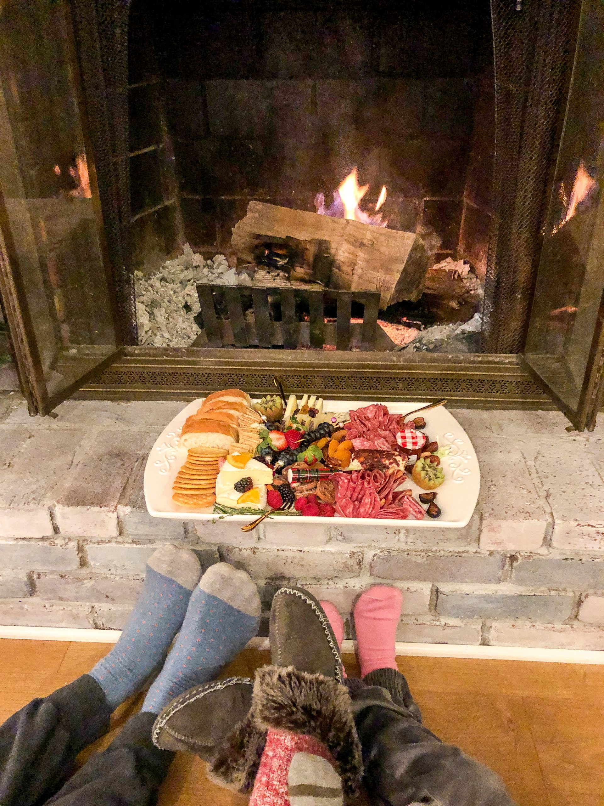 Meat and Cheese platter in front of fire with family's feet in front of it