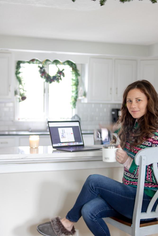 woman sitting at counter with laptop holding coffee mug