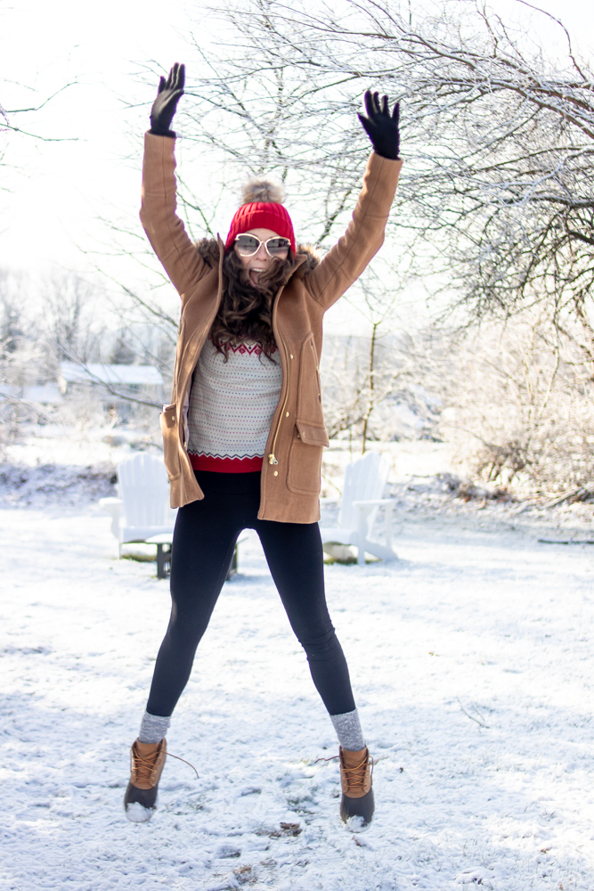 girl wearing winter clothes jumping in the air in the snow