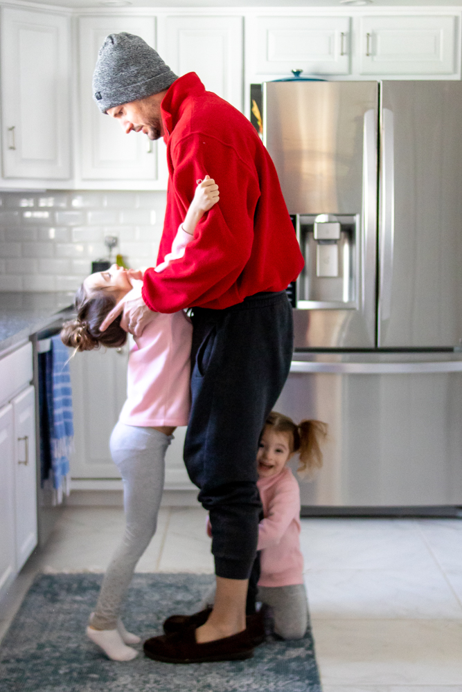 Dad in kitchen with kids hanging off of him