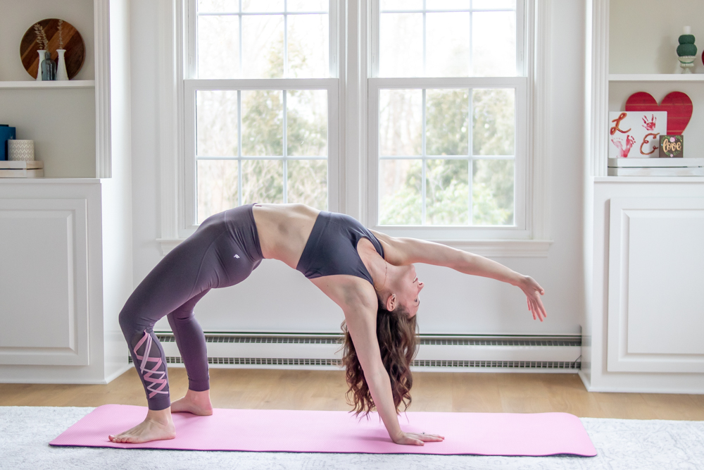 woman doing wheel in yoga with arm raised