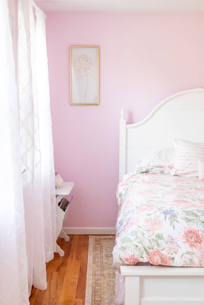 pink bedroom walls, white bed with floral bedding, white sheer curtains