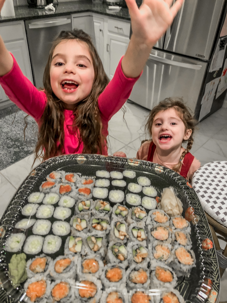little girls cheering as they look at sushi