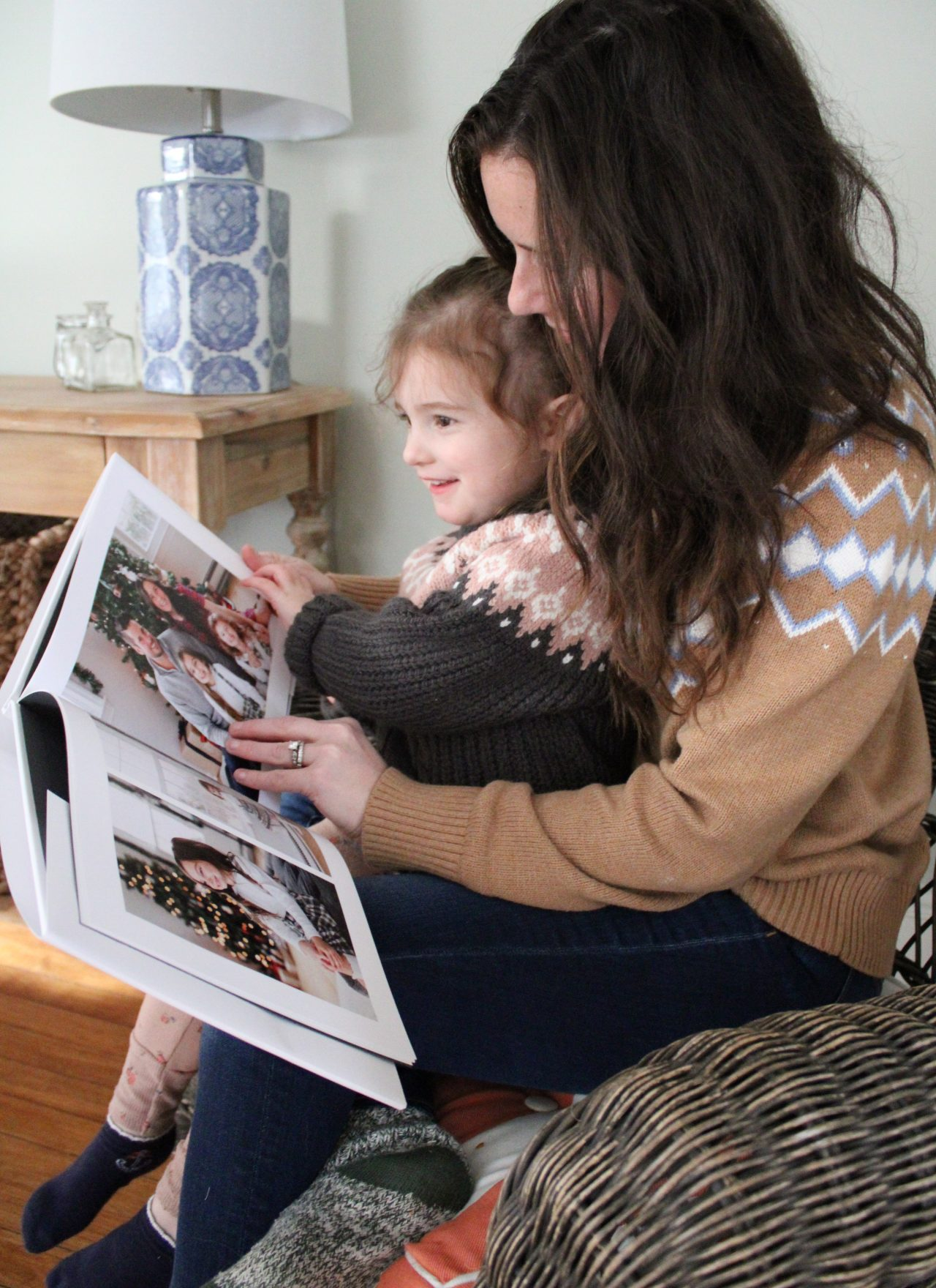 mom looking at photo book with daughter