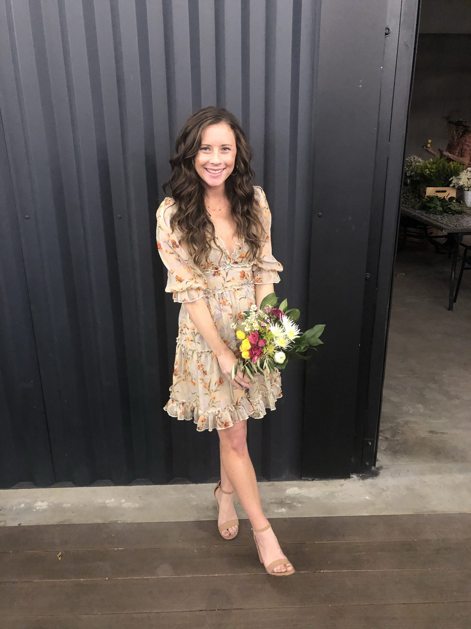 woman in tan floral dress holding bouquet