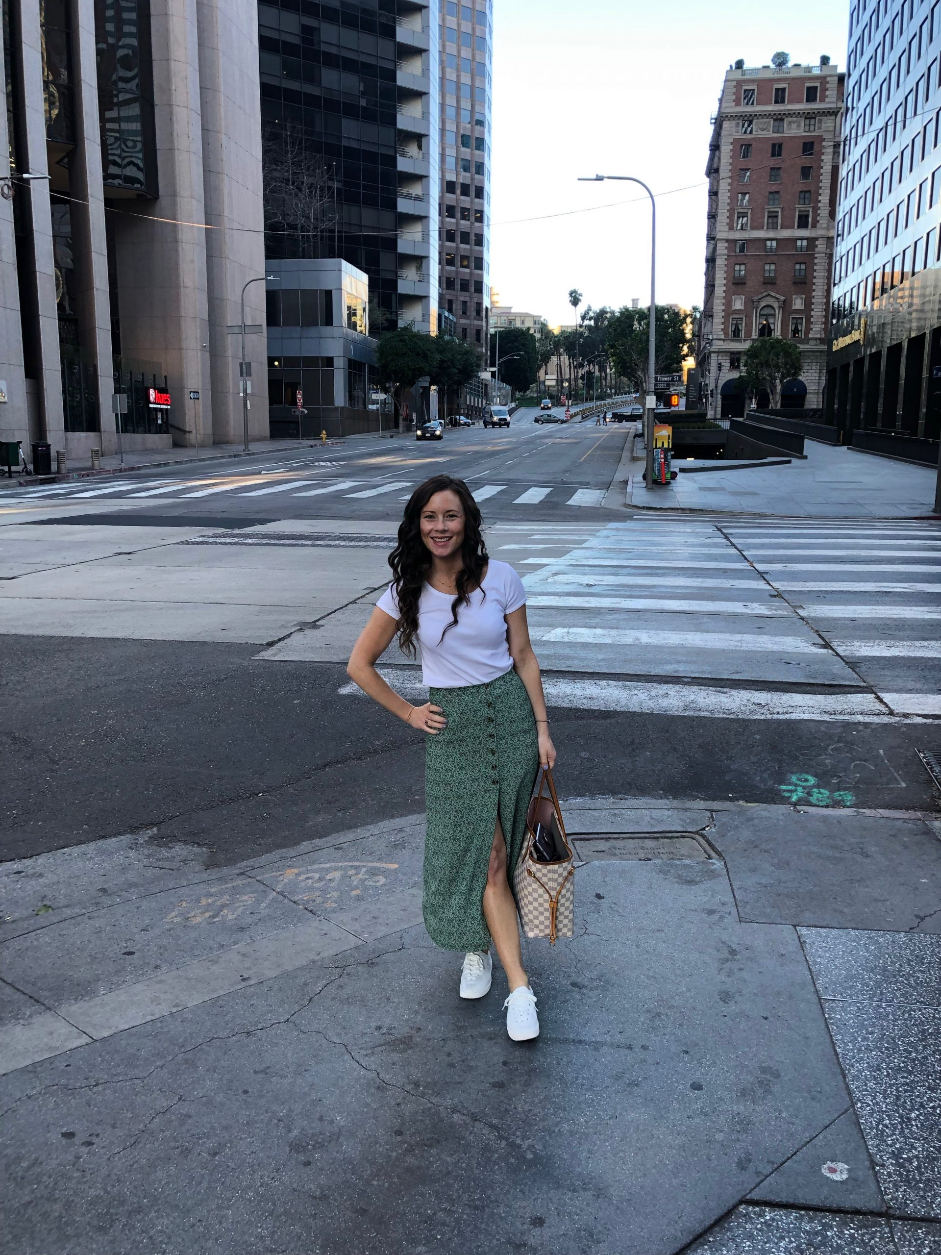 woman standing on street in downtown LA wearing a white shirt, green skirt, white sneakers